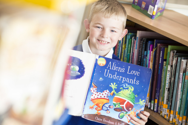A boy looking at the camera holding a book